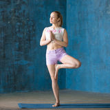 Beautiful sporty young woman Doing Tree Pose. Portrait of beautiful young woman dressed in shorts and white top enjoying yoga indoors. Yogi girl working out in Royalty Free Stock Photography