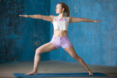 Beautiful sporty young woman Doing Warrior II posture Royalty Free Stock Photos