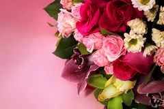 Beautiful spring bouquet of flowers close-up on a pink background. Bouquet of roses, chrysanthemums, lilies. Stock Photos