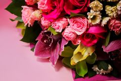 Beautiful spring bouquet of flowers close-up on a pink background. Bouquet of roses, chrysanthemums, lilies. Royalty Free Stock Image