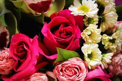 Beautiful spring bouquet of flowers close-up on a pink background. Bouquet of roses, chrysanthemums, lilies. Stock Photo