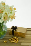 Daffodils in vase. Beautiful spring daffodils in a glass vase with heart shaped chocolates and box Royalty Free Stock Image