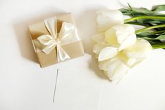 Beautiful spring holidays flowers arrangment. Bunch of white tulips in festive composition, copy space for text, white background. Feminine festive composition Royalty Free Stock Photos