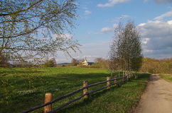 Beautiful spring landscape with birches, road, meadow and church. Royalty Free Stock Photography