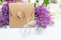 Beautiful spring lilac little white bike and gift box on a background Stock Images