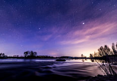 Beautiful spring night at riverbank. Beautiful spring night and starlit sky by the river. Fascinating colors appeared in the sky Stock Images