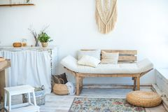 Beautiful spring photo of kitchen interior in light textured colors. Kitchen, living room with beige couch sofa, large cactus and. Woven macrame on the wall stock photography