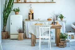 Beautiful spring photo of kitchen interior in light textured colors. Kitchen, living room with beige sofa sofa, old retro white fr. Idge, rustic table, large stock images