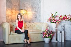 Beautiful spring photography in the decorated interior. A young woman sits on a white leather sofa. At home Stock Photos