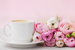 Beautiful spring Ranunculus flowers and cup of coffee on stone table. Pastel color. Greeting card for Valentines or Womans Day stock images