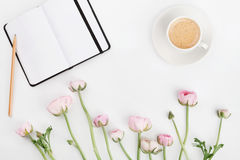 Beautiful spring Ranunculus flowers, empty notebook and cup of coffee on white desk from above. Greeting card. Breakfast. Flat lay