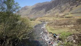 Beautiful spring sunshine Glencoe river Clachaig Scotland UK with mountains in Scottish Highlands in spring with people stock video footage