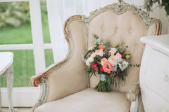Beautiful spring wedding bouquet of roses and eucalyptus on a beige vintage armchair Royalty Free Stock Photos