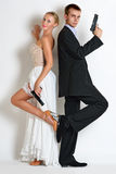 Beautiful spy couple in evening dress with a guns. Stock Photos