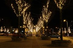 A beautiful square in Frydek-Mistek in czech republic surrounded by christmas trees. A bulbs lighting on trees along car parking.  stock images