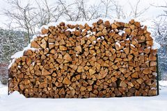 Beautiful stack of chopped firewood in snowy country, sunny winter stock photography