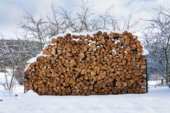 Beautiful stack of chopped firewood in snowy country, sunny winter royalty free stock photography