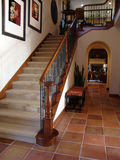 Beautiful Staircase. Leading up to a family room. Office or study can bee seen from entry. Mexican tile floors carpet on steps beautiful wood banisters Stock Photography