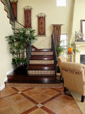 Beautiful Staircase. Beautiful tiled entry leading to elegant wood staircase Royalty Free Stock Photo