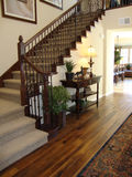 Beautiful Staircase and Entry. Beautiful staircase with wood floors and wood handrails or banister table lamp plant rug stock images