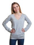 Beautiful standing woman in a grey sweater with crossed arms Stock Image