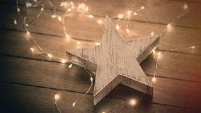 beautiful star shaped toy and bright cute garland lying on th wonderful brown wooden background royalty free stock photos