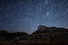 Beautiful star trails time-lapse over the hills. Polar Star at the center of rotation. Lateral light from the full moon on the chalk hills.Cretaceous Hills Royalty Free Stock Images