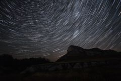 Beautiful star trails time-lapse over the hills. Polar North Star at the center of rotation. Lateral light from the full moon on the chalk hills. 4K resolution Royalty Free Stock Photography