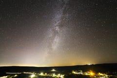 Beautiful starry dark night sky over rural landscape. Dark green hills, bright lights of road. royalty free stock photos