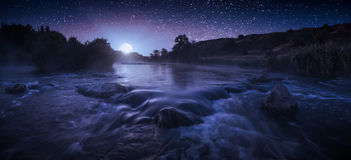 Beautiful starry night above the river. In a light of rising moon stock photos