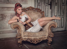 Beautiful steampunk woman on the armchair. Beautiful steampunk woman with pink hair on the armchair Royalty Free Stock Photos