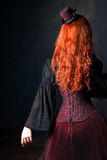 Beautiful steampunk woman back. Slender red-haired girl in corset and hat Royalty Free Stock Images