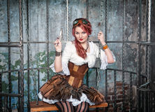 Beautiful steampunk woman in the cage with gun Stock Photography