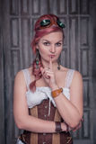 Beautiful steampunk woman in corset making silence gesture Royalty Free Stock Photography
