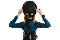 Beautiful steampunk woman with hat isolated. Beautiful elegant steampunk retro woman covering her face with black hat studio shot isolated on white background royalty free stock photography