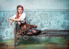 Beautiful steampunk woman on the metal bed Royalty Free Stock Images