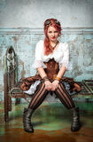 Beautiful steampunk woman on the metal bed royalty free stock image