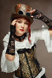 Beautiful steampunk woman. Portrait of beautiful steampunk woman wearing vintage hat and corset posing next to color background Stock Image