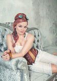 Beautiful steampunk woman on the sofa Royalty Free Stock Photography