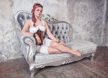 Beautiful steampunk woman on the sofa royalty free stock photos