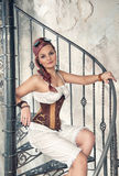 Beautiful steampunk woman on the stairway Stock Photography
