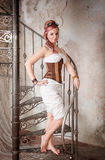 Beautiful steampunk woman with trousers on the stairway Royalty Free Stock Photos