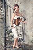 Beautiful steampunk woman with whip on the stairway Stock Image