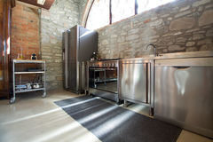 Beautiful steel kitchen in rustic interior. Beautiful professional steel kitchen in rustic interior Royalty Free Stock Images