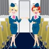 Beautiful Stewardess. Two beautiful stewardess in blue uniforms inside an airliner passenger cabin Stock Image