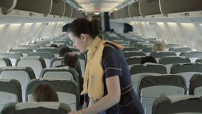Beautiful stewardess checks the safety of passengers at the airplane stock video footage