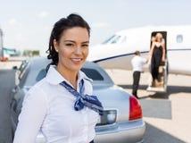 Beautiful Stewardess Standing Against Limousine stock photos
