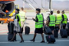 Beautiful stewardesses dressed in official dark blue uniform of Aeroflot Airlines and reflective vests go to plane on airfield. royalty free stock photography
