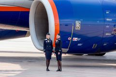 Beautiful stewardesses dressed in official dark blue uniform of Aeroflot Airlines stand near at Rolls Royce`s jet engine royalty free stock photography