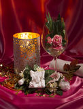 Beautiful still life with candle, wineglass and necklace on pink silk Stock Photography